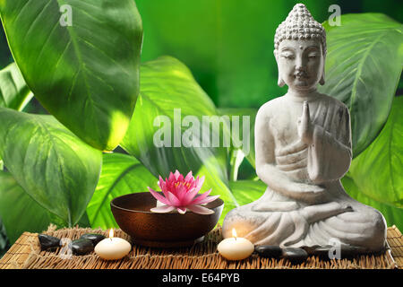 Buddha in meditation with lotus flower and burning candles - Stock Photo