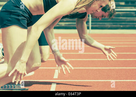 Race of male and female track and field athletes in a stadium. Vintage photo variant - Stock Photo
