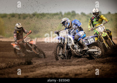 Three motocross riders on a track during a race, Grevenbroich, North Rhine-Westphalia, Germany - Stock Photo
