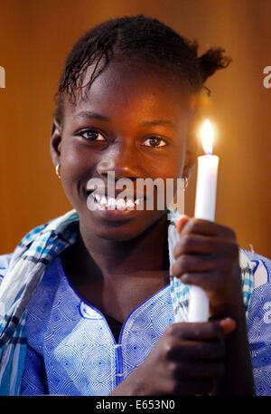 Girl (11 years) holding candle in a catholic church in Kaolack, Senegal, Africa - Stock Photo