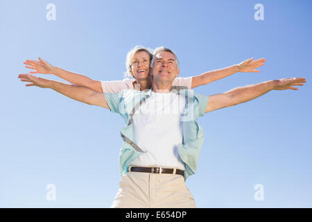 Happy senior man giving his partner a piggy back - Stock Photo