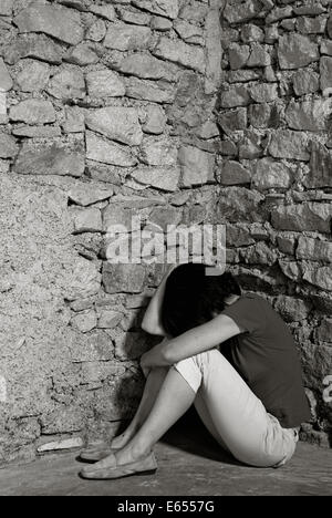 Depressed middle-aged woman sitting with head in hands in a room corner - Stock Photo