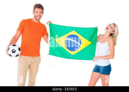 Excited football fan couple holding brazil flag - Stock Photo