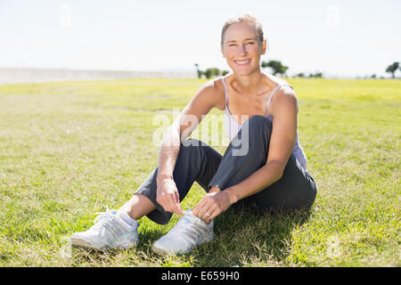 Fit mature woman tying her lace on the grass - Stock Photo