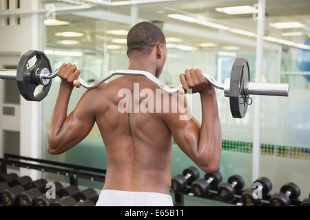 Rear view of shirtless man lifting barbell in gym - Stock Photo