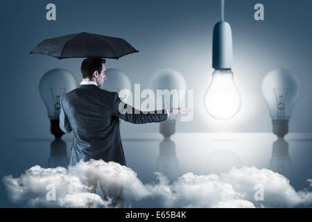Composite image of businessman holding an umbrella with hand out - Stock Photo
