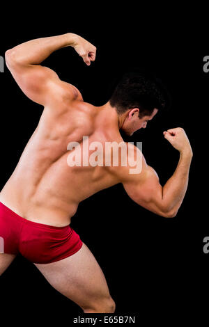 Rear view of a shirtless muscular man flexing muscles - Stock Photo