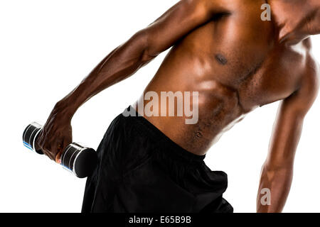 Mid section of fit shirtless young man lifting dumbbell - Stock Photo