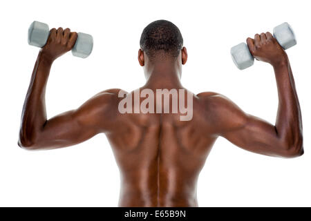 Rear view of a fit shirtless man lifting dumbbells - Stock Photo