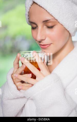 Beautiful woman in bathrobe having tea - Stock Photo