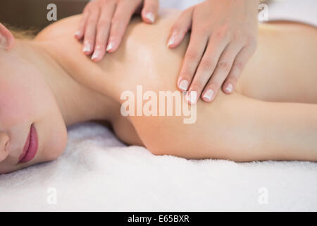 Woman receiving shoulder massage at spa center - Stock Photo