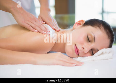 Attractive young woman receiving shoulder massage at spa center - Stock Photo