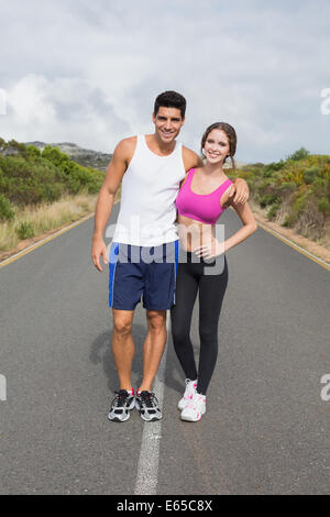 Portrait of a fit couple standing on road - Stock Photo