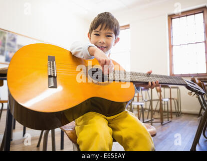 Cute pupil playing guitar in classroom - Stock Photo