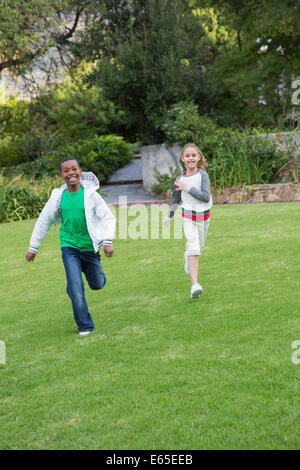 Happy young friends running towards the camera - Stock Photo