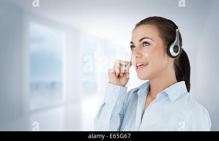 Composite image of call center agent looking upwards while talking - Stock Photo