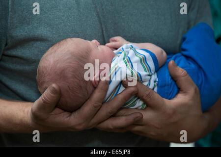 Denver, Colorado - Adam Hjermstad holds his two-week-old son, Adam Hjermstad Jr. - Stock Photo