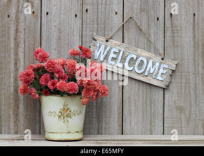 Rustic welcome sign hanging on weathered wood fence next to pot of flowers - autumn mums - Stock Photo