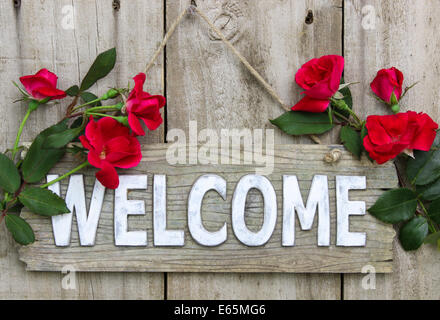 Weathered wood welcome sign hanging on wooden door with flower border of red roses - Stock Photo