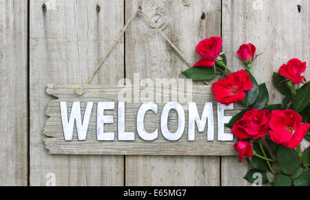 Distressed welcome sign hanging on wood fence with flower border of red roses - Stock Photo