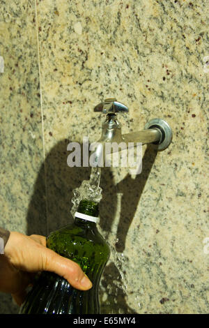 Hand Holds a bottle to fill with mineral water from the tap - Stock Photo