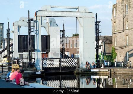 People enjoying the summer evening sun next to Leamington Lift Bridge on the Union Canal, Edinburgh Quay - Stock Photo