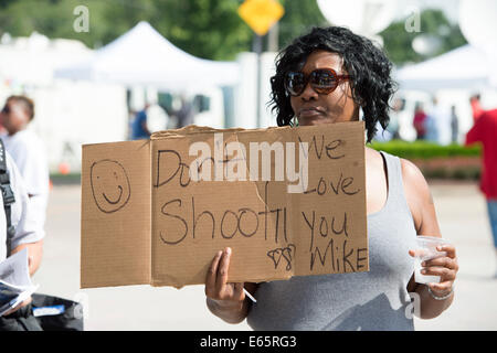 Ferguson, Mo., US. 15th Aug, 2014. Woman at the Site of destroyed Quick Trip Holds sign after Police Chief Thomas Jackson release of the name of the officer that shot Michael Brown. Credit:  Gino's Premium Images/Alamy Live News