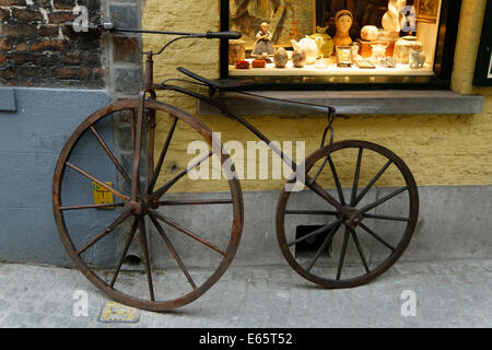A 19th-century bicycle leans against an  antique shop wall and its illuminated window in Bruge - Stock Photo
