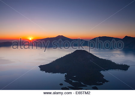 The rising sun clears the eastern caldera rim of Crater Lake, Oregon. Wizard Island, a dormant volcanic cone formed - Stock Photo