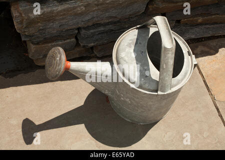 Galvanized metal watering can sits on a flagstone patio. - Stock Photo