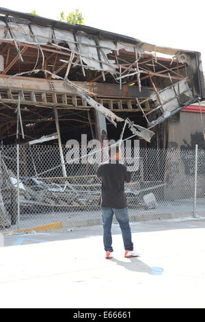 Ferguson, MO, USA. August 15, 2014. Demonstrator in front of destroyed Quick Trip after Police Chief Thomas Jackson release of the name of the officer that shot Michael Brown.