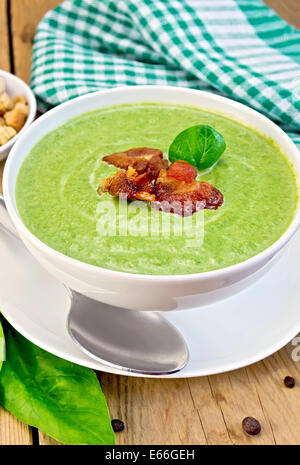 Green soup puree in a white bowl with spinach and grilled meat, napkin, crackers, spoon on a wooden boards background - Stock Photo