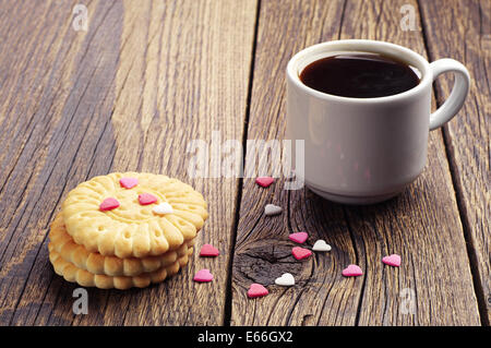 Cup of coffee and cookies with small sweet hearts on vintage wooden table - Stock Photo