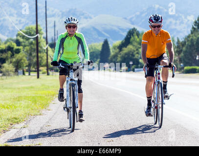Middle aged man & woman riding bikes on country road - Stock Photo