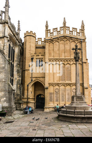 15th century south porch of the historic Church of St John Baptist, with people sitting outside, Cirencester, Cotswolds, - Stock Photo