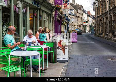 People sitting outside a cafe restaurant in a side street of shops in Cirencester town centre, Cotswolds, Gloucestershire, - Stock Photo