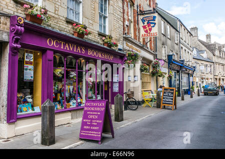 Octavia's Bookshop painted a vivid purple, alongside other shops in a side street of Cirencester town centre, Cotswolds, - Stock Photo