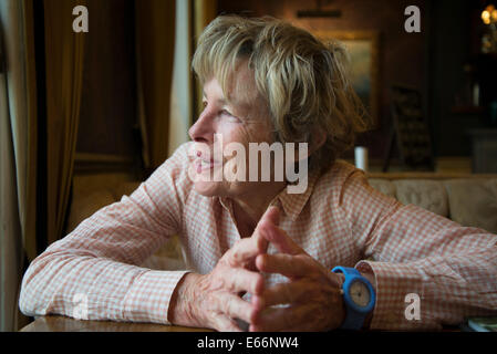 Elderly woman looking out of the window smiling - Stock Photo
