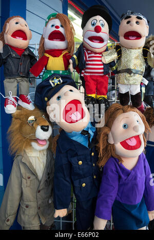 Display of funny colourful puppets outside toy shop. - Stock Photo
