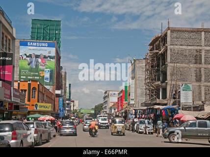 People and traffic on Kenyatta Avenue Nakuru Kenya East Africa with advertising hoardings shops and Piaggio Ape - Stock Photo