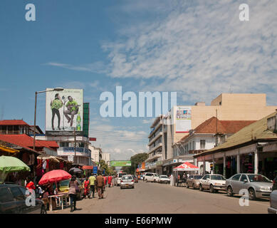 People and traffic on Kenyatta Avenue Nakuru Kenya East Africa with advertising hoardings modern and old fashoned - Stock Photo