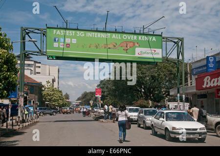 People and traffic on Kenyatta Avenue Nakuru Kenya East Africa with advertising hoarding for 3g Network - Stock Photo