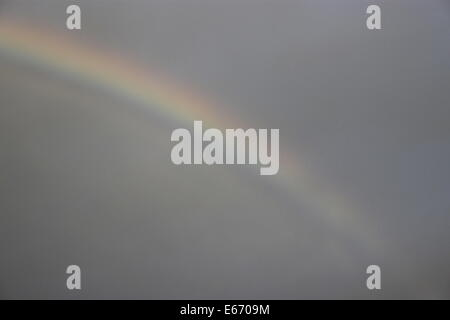 Rainbow against grey sky with evening sun in Beverley, East Yorkshire, England - Stock Photo