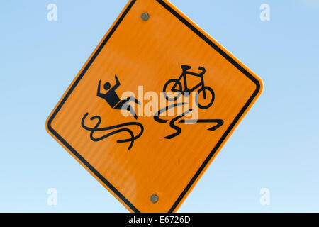 Slippery when wet sign illustrating human and bike on slippery road surface - Stock Photo