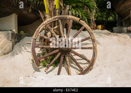 Old brown wooden wheel on sand beach. - Stock Photo