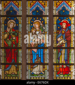 BRUGES, BELGIUM - JUNE 13, 2014: Madonna with the saints on the windowpane in st. Giles church (Sint Gilliskerk) - Stock Photo