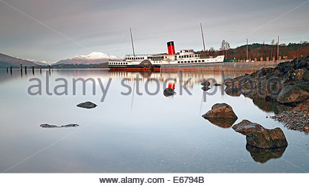 The Maid of the Loch paddle steamer and the snow capped mountain of Ben Lomond by Loch Lomond shores. - Stock Photo