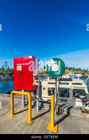 Brightly coloured red fire hydrant and green extension hose on Eden Wharf, Eden Harbour, NSW Australia - Stock Photo