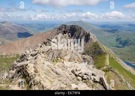 Hikers scrambling on Crib y Ddysgl with view back to Crib Goch ridge on Snowdon Horseshoe in Snowdonia North Wales - Stock Photo