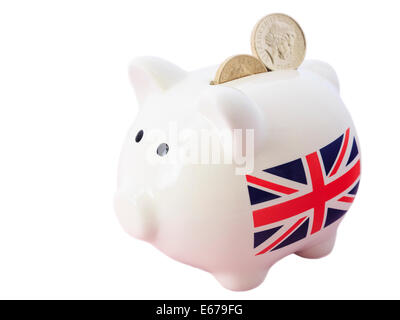 Piggy bank with British Union Jack and sterling pound coins in slot to illustrate saving money financial growth - Stock Photo